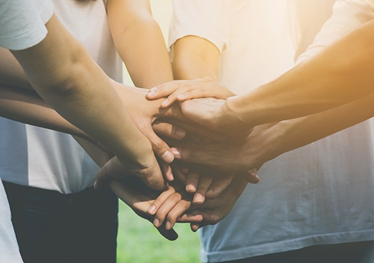 Group of people in a circle with their hands together