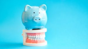 blue piggy bank on top of dentures