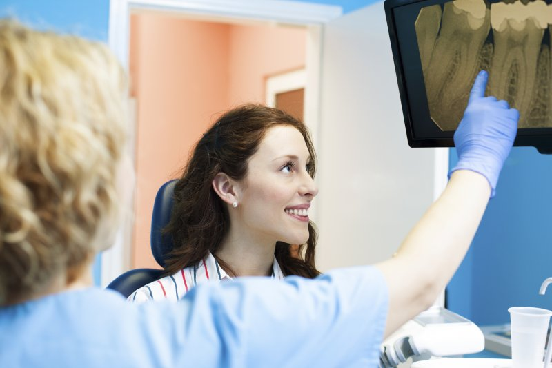A dentist pointing at a dental X-ray for a patient.