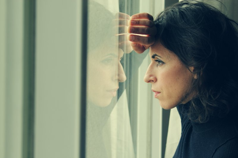 A woman looking outside a window.