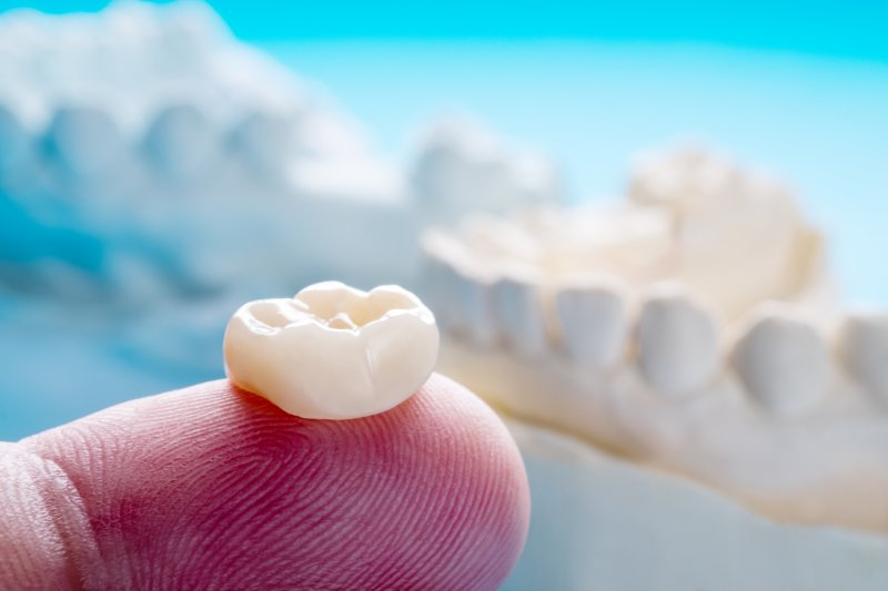an up-close look at a person's finger holding a customized dental crown